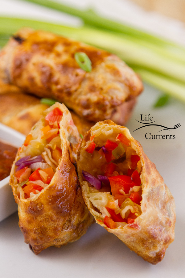 Vegetable egg rolls witg one cut open so you can see the inside