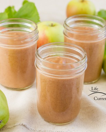 3 mason jars full of Instant Pot Apple Butter with some apples around and some leaves