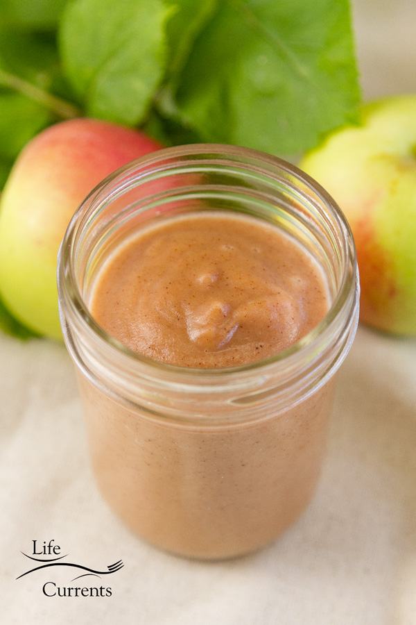 a mason jar with apple butter inside and a couple of fresh apples with leaves behind it