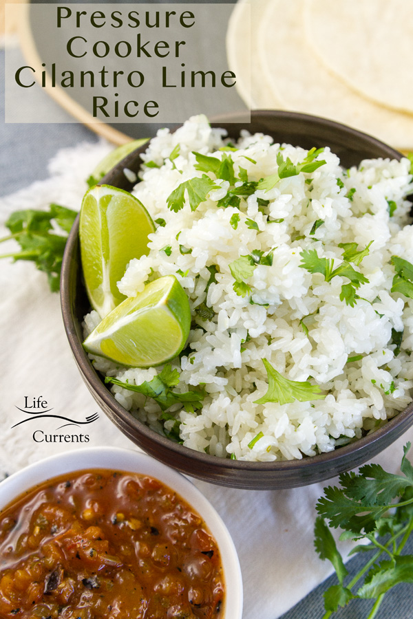 a bowl full of cilantro lime rice with wedges of lime served with salsa and corn tortillas