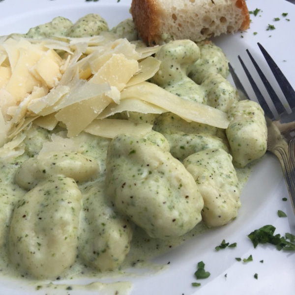 gnocchi in a creamy pesto sauce with parmesan and bread