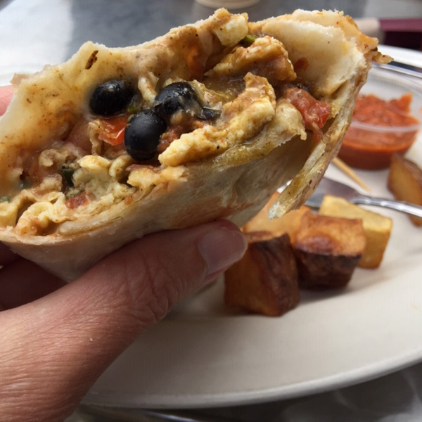 A breakfast burrito that's cut in half so you can see inside
