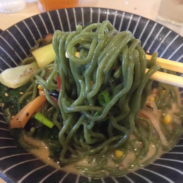 green kale noodles in a bowl of ramen being held up by chopsticks