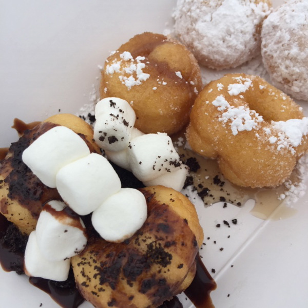 Three different flavors of mini dounuts: S'mores, French toast, and powdered sugar