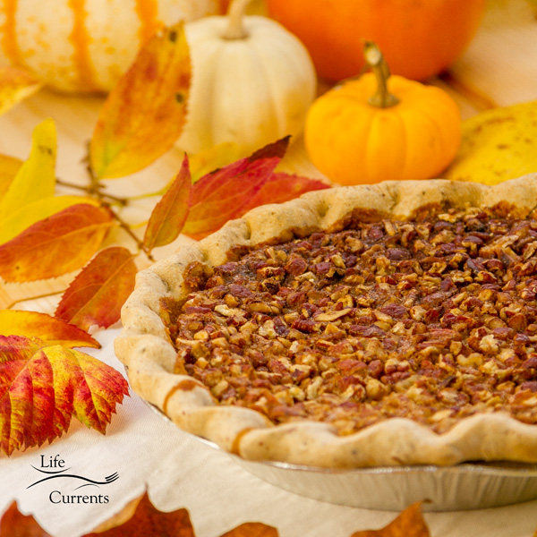 a pecan pie in the tin surrounded by fall leaves and pumpkins