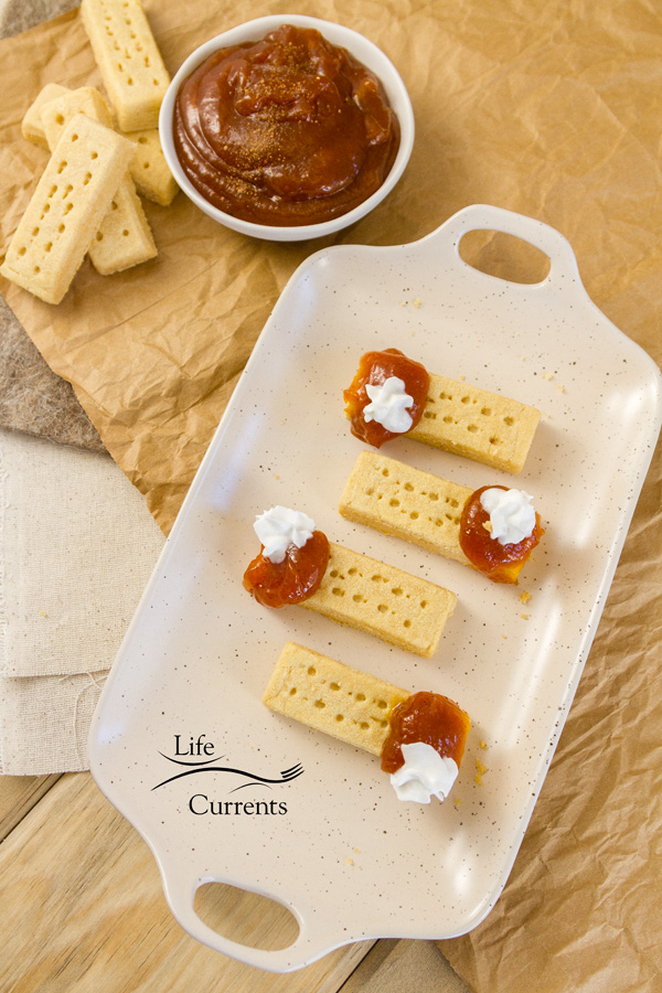 A tray full of Pumpkin Butter pie bites with a bowl of pumpkin butter and shortbread cookies on the side