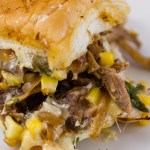 a close up on the carnitas slider sandwich with Mexican Street Corn (esquites), caramelized onions, and cheese