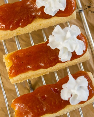 Pumpkin Pie Bites with whipped cream on a cooling rack, square image