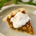 a piece of pecan pie with fluffy billowy Peach Caramel Whipped Cream over it on a plate with fir branches in the background
