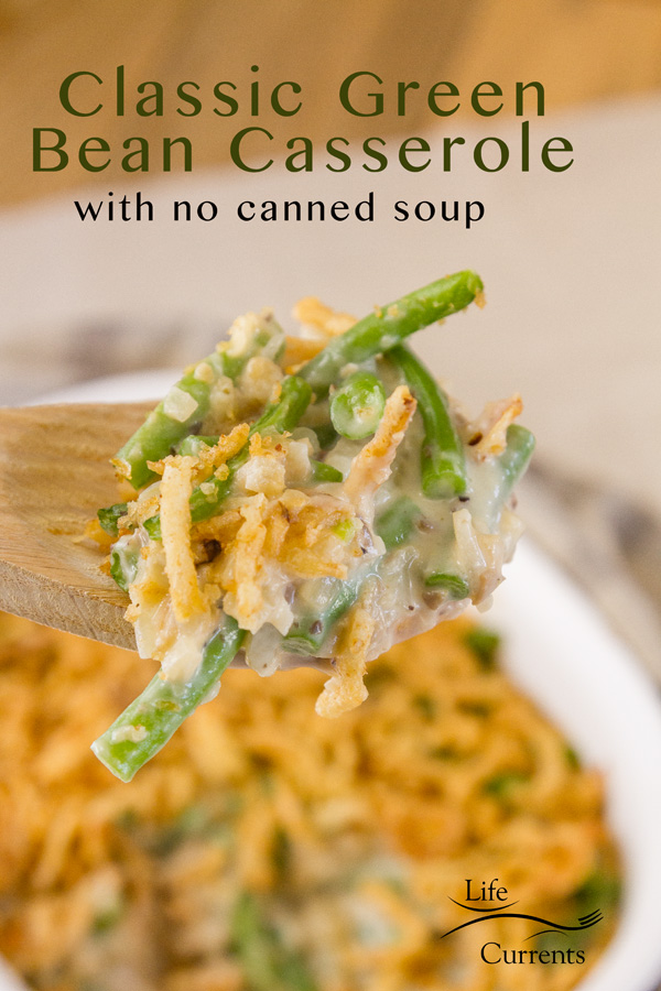 Green bean casserole served from a wooden spoon with the casserole in the background