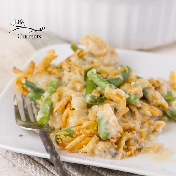 Square cropped image of green bean casserole on a white plate with a fork