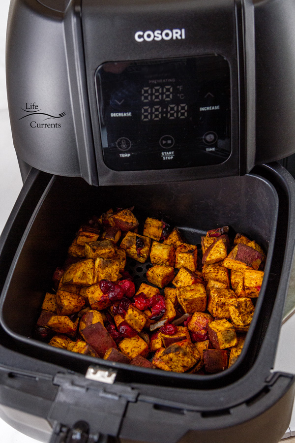 sweet potatoes in the basket of an air fryer