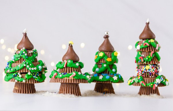 4 Chrismas trees made from peanut butter cups standing next to each other