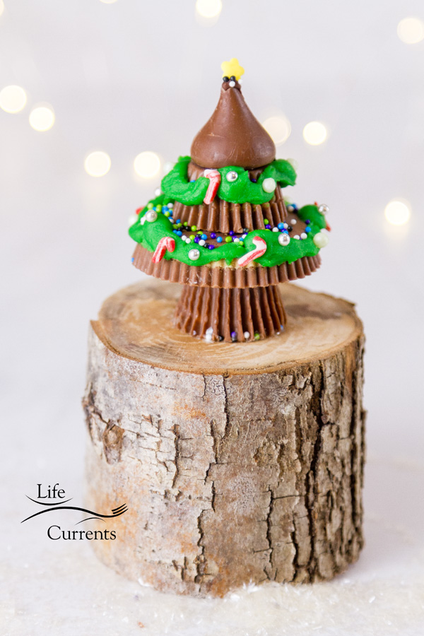 A Christmas tree made from peanut butter cups on a wooden stand