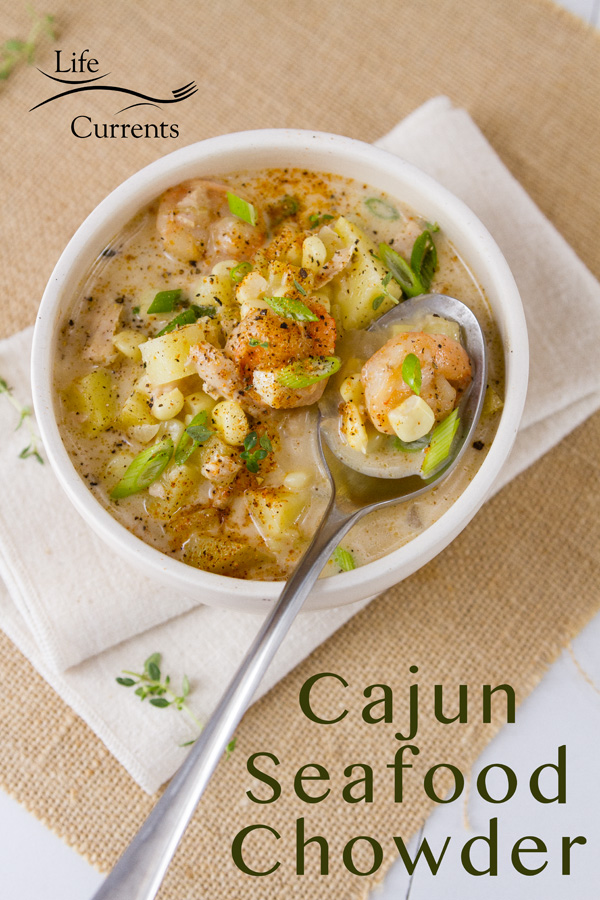 A bowl of Cajun seafood chowder in a white bowl with shrimp, potatoes, corn, and green onions, and a spoon on a napkin