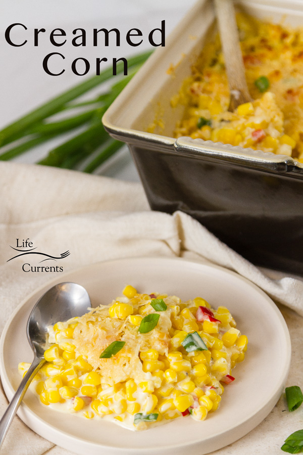 A serving of Creamed Corn on a plate with the side dish in the background and the title