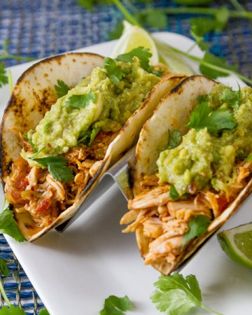 square crop of two tacos on a white plate