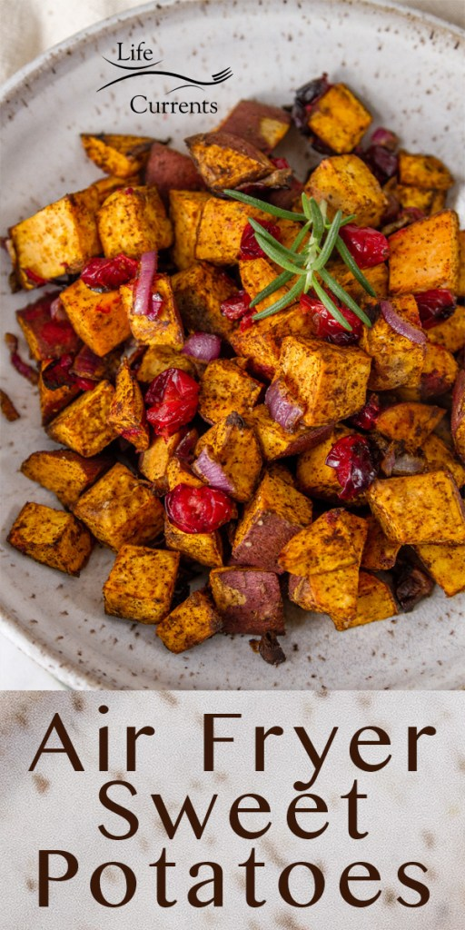 cubed sweet potatoes, cranberries, and red onions roasted and served in a white bowl garnished with rosemary