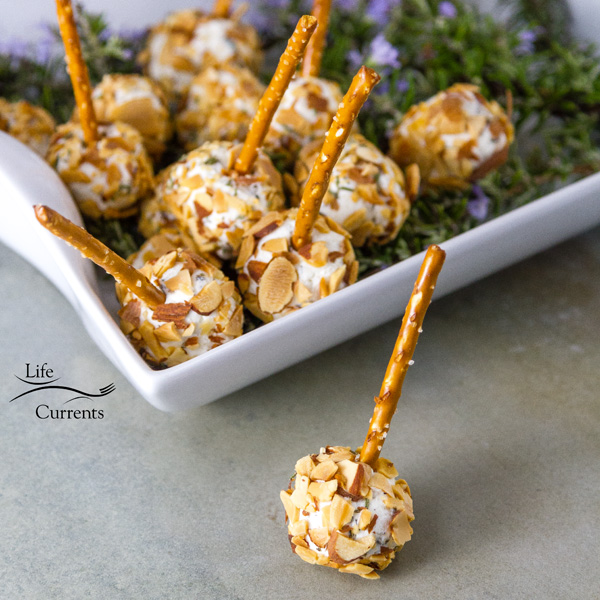 Pepper Jelly Cheese Balls in a serving platter on top of fresh rosemary and one has been taken out and placed in front of the tray