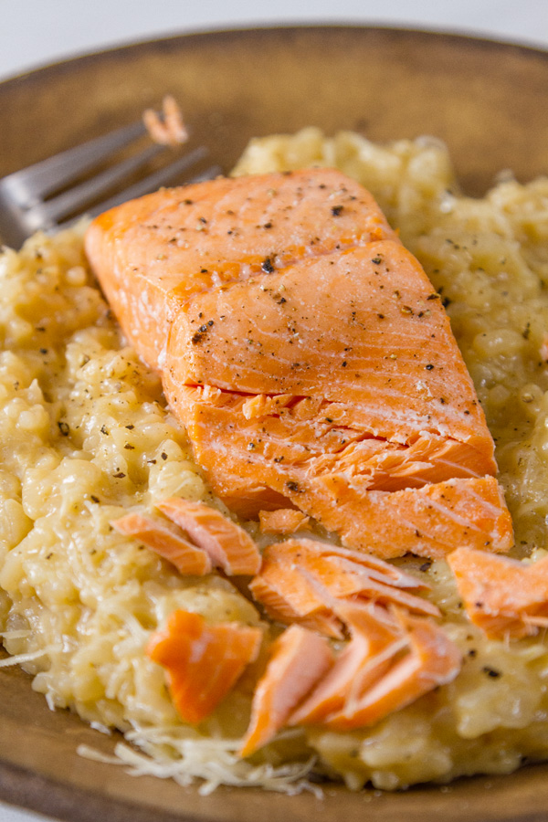 Roasted Salmon Risotto served in a brown bowl with a fork