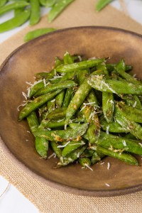 Air Fryer Parmesan Sugar Snap Peas on a brown plate with some raw pea pods in the background