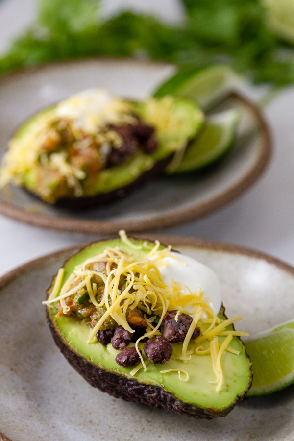 Two 4 Layer Stuffed Avocados on white plates with lime wedges and cilantro leaves