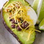 up close shot of 4 Layer Stuffed Avocados with lime wedges