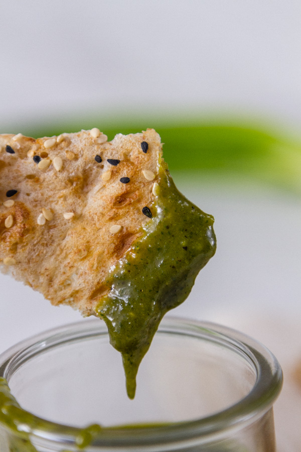 a piece of bread dipped into Tamarind Cashew Dipping Sauce