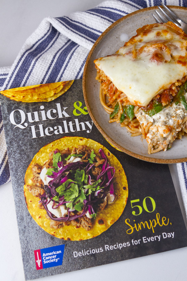 Spinach Provolone Baked Pasta from the book Quick & Healthy 50 Simple, Delicious Recipes for Every Day by the American Cancer Society both the book and the meal are pictures with a blue striped towel