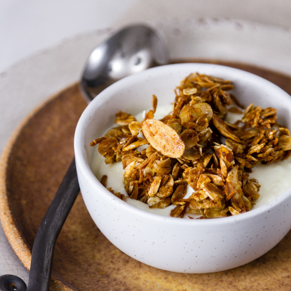 Homemade Granola Recipe in a white bowl served over yogurt, with a spoon on the left