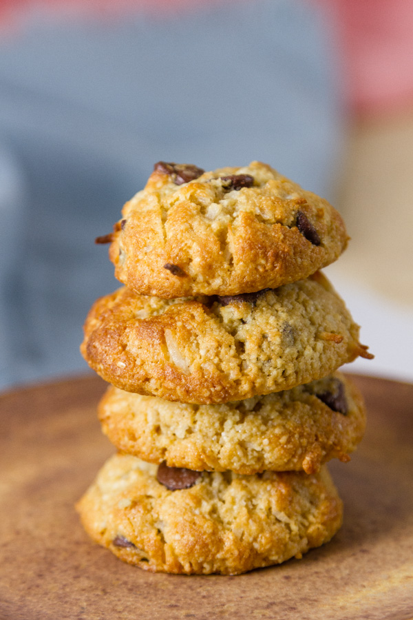 Coconut Almond Meal Cookies with Chocolate Chips stcaked up on top of each other with a blue cloth in the background