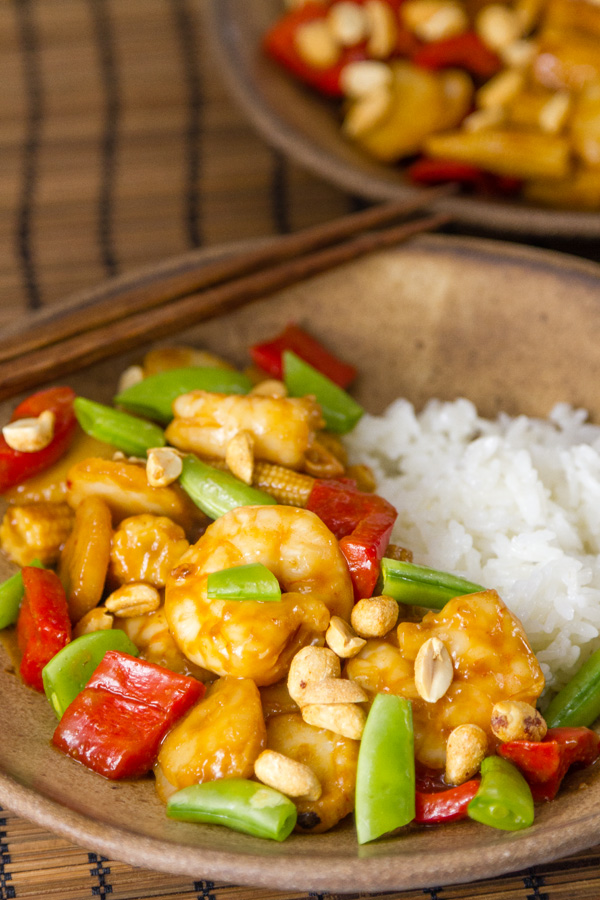 Air Fryer Kung Pao Shrimp with snap peas on top served with rice in a brown bowl