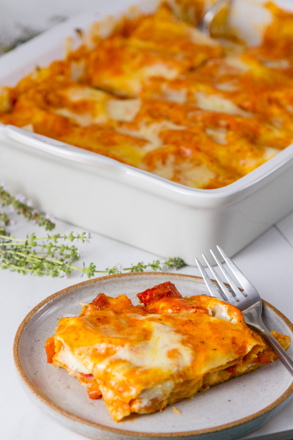 Red Pepper Lasagna - one serving on a plate with the casserole in the background