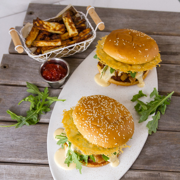 top down or flat lay shot of two Monster Cheese Burgers on a white platter with french fries and ketchup on wooden slats