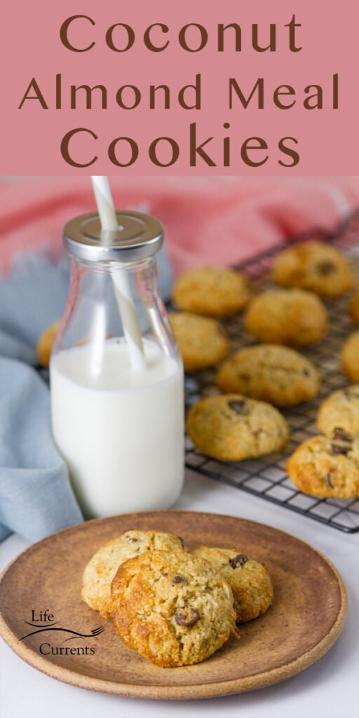Coconut Almond Meal Cookies with Chocolate Chips on a brown plate with a glass of milk and more cookies on the cooling rack with some pink and blue napkins