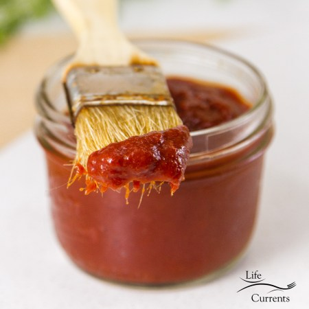 Zesty No-Cook BBQ Sauce in a jar with a brush that's been dipped in the sauce