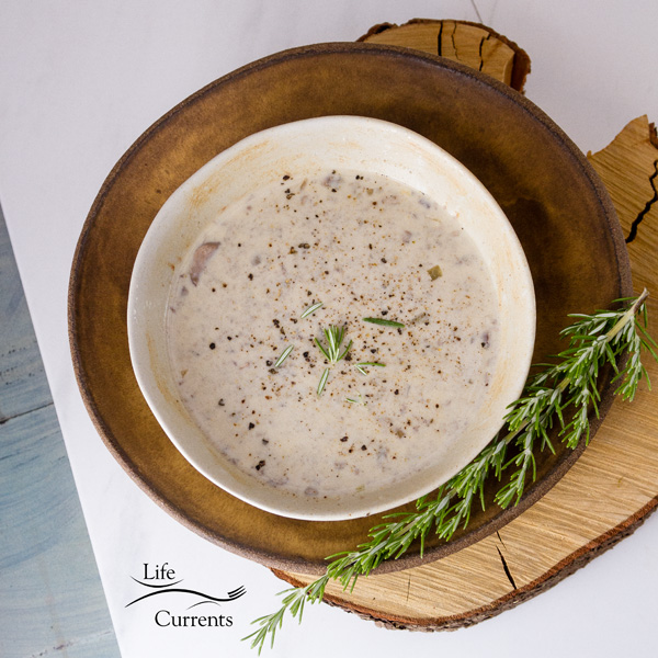 a bowl full of Copycat Souplantation Vegetarian Cream of Mushroom Soup top down shot on a brown plate with a sprig of rosemary in the lower right, square crop