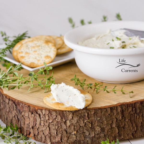 square crop of Garlic and Herb Cheese Spread in a white bowl with crackers and fresh herbs