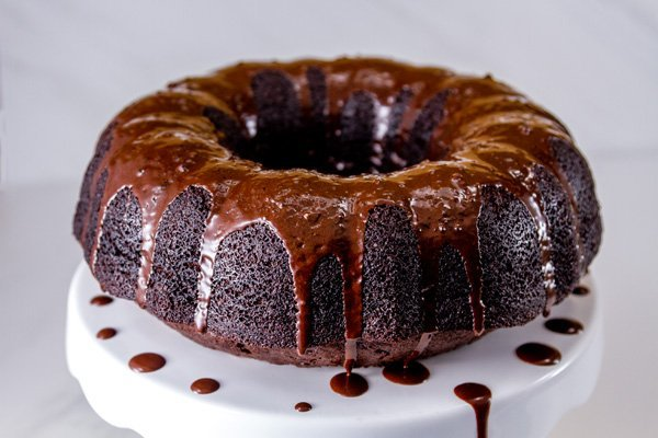 From Scratch Dark Chocolate Cake glazed with mocha icing on a white cake plate with drips of icing falling off