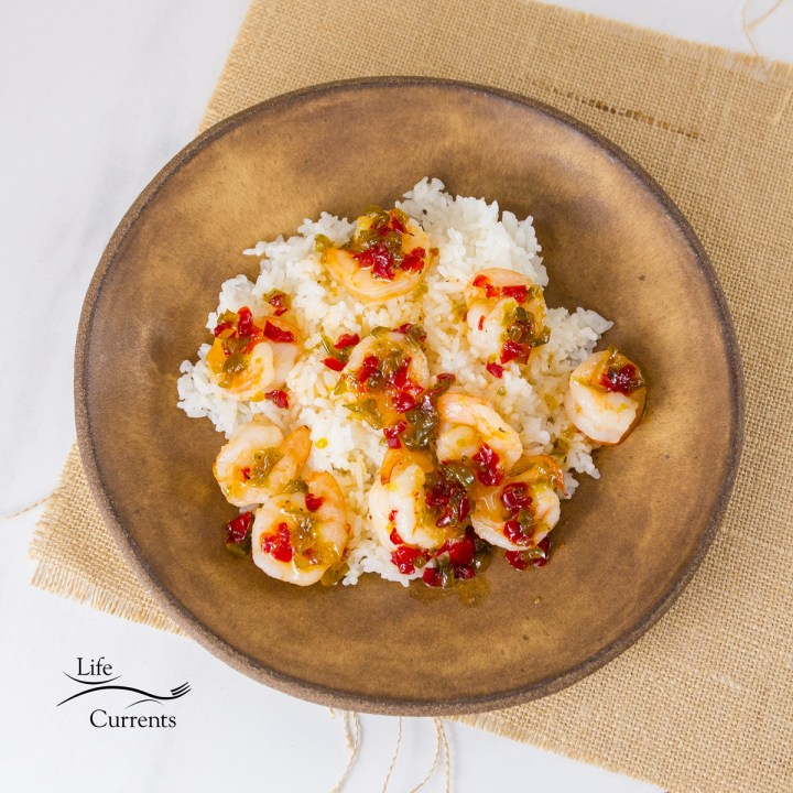 square crop of top down shrimp on rice with sauce in a brown bowl