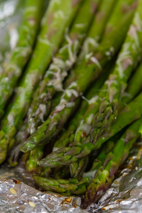 close up of cooked asparagus on foil with Parmesan cheese