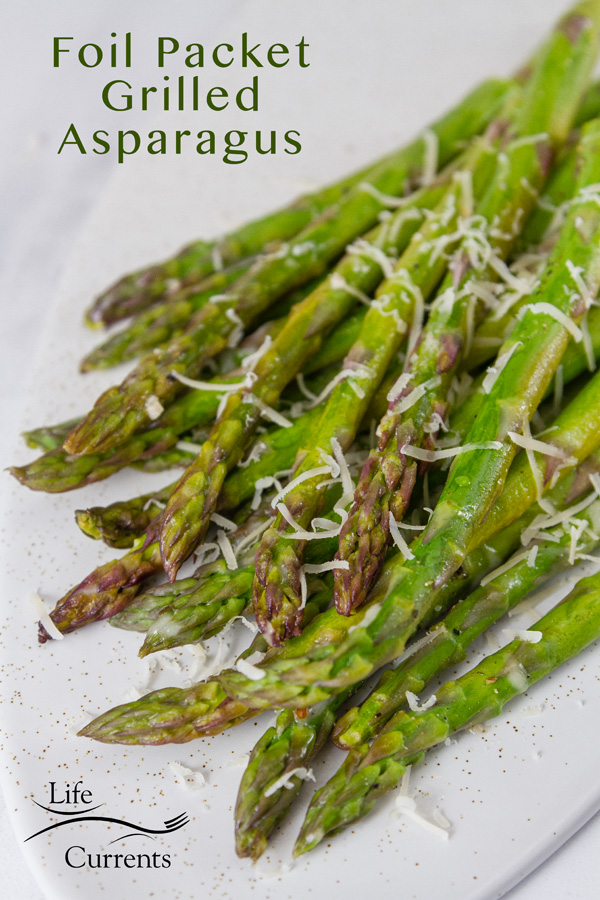 grilled asparagus on a white plate sprinkled with grated Parmesan cheese. Title in the top left: Foil Packet Grilled Asparagus