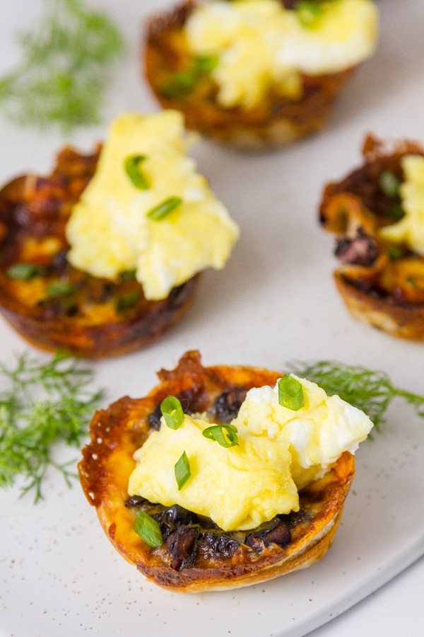 Chilaquiles Cups: filled with enchilada sauce, cheese, and black beans topped with scrambled eggs, green onions served with cilantro garnish