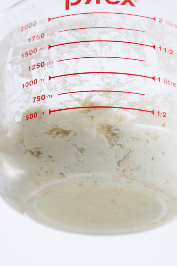 looking at the side & the bottom of the bread dough in a measuring cup