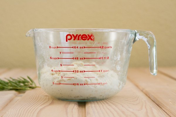 a 2-quart glass measuring cup with bread dough in it on a wood board