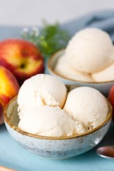 two bowls of ice cream with peaches and flowers around them
