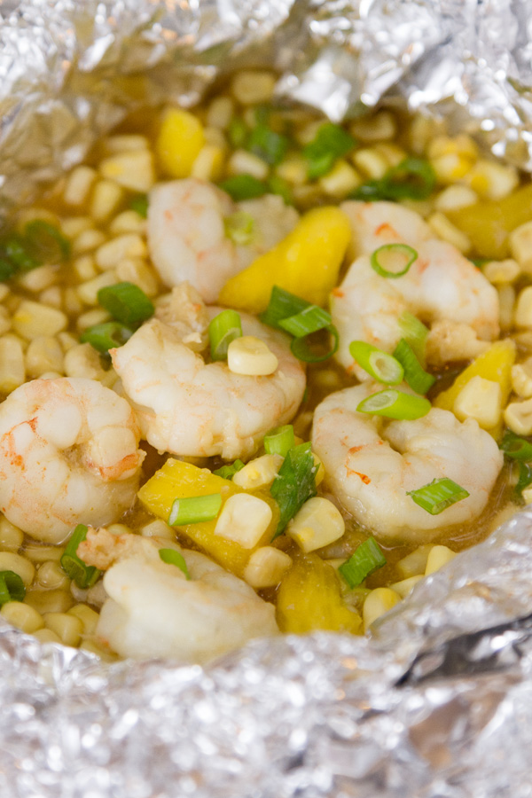 close up on an open Foil Packet of Caribbean Shrimp with shrimp, corn, pineapple, and green onions