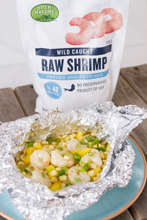 Foil Packet Caribbean Shrimp still in the foil on a blue plate with a bag of Open Nature Raw Shrimp in the background