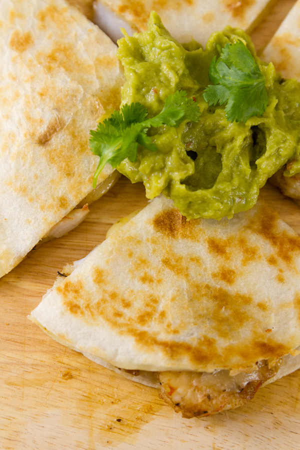 close up on a shrimp quesadilla wedge served with guacamole and garnished with cilantro