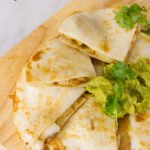shrimp quesadillas cut into triangles on a wood cutting board served with guacamole and cilantro